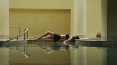 WS Young woman lying by indoor swimming pool / Petriolo,Marche,Italy Stock Footage