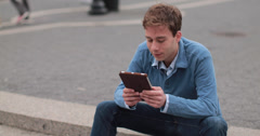 Young Caucasian man in city using tablet pc computer - stock footage