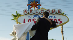 MONTAGE MS LA Newly wed couple dancing and kissing by Las Vegas welcome sign / Stock Footage