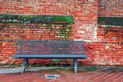 metal bench and old brick wall in alba, italy. - stock photo