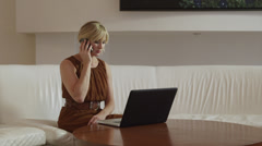 WS Woman using laptop and talking on mobile phone in a lobby / South Beach, Stock Footage