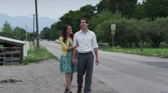 SLO MO WS Young couple walking along rural road / Pleasant Grove, Utah, USA Stock Footage