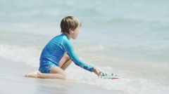 SLO MO MS Boy (6-7) playing with toy boat in ocean / South Beach, Miami, - stock footage