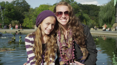 MS PAN Portrait of two teenage girls sitting on edge of pond in Central Park / Stock Footage