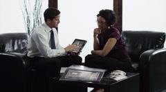 MS Business couple having meeting in lobby using digital tablet/ Orem, Utah, USA - stock footage