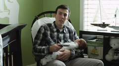 MS ZI Father playing on mobile phone, sitting with baby boy in rocking chair in Stock Footage