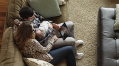 HA MS Couple using digital tablet, sitting with baby son (0-1 months) on sofa / Stock Footage