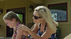 SLO MO MS PAN Mother rubbing daughter (8-9) with suntan lotion on patio / Cedar Stock Footage