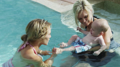 MS Adults playing with baby boy (6-11 months) in pool / Cedar Hills, Utah, USA Stock Footage