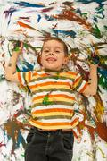 Happy messy boy lying on panted background Stock Photos