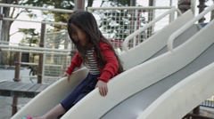 USA, California, San Francisco, Alamo Square Park, Girl (4-5) sliding in Stock Footage