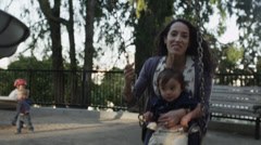 USA, California, San Francisco, Alamo Square Park, Mother swinging with son Stock Footage