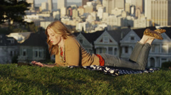 USA, California, San Francisco, Alamo Square Park, Woman lying on grass and Stock Footage