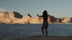 WS DS Rear view of young woman dancing near Lake Powell / Utah, USA Stock Footage