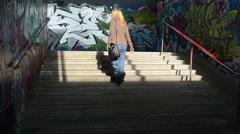 Blond woman walk upstairs city underground dark passage subway Stock Footage