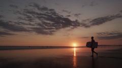 Costa Rica, Esterillos Beach, Mature surfer walking on beach at sunset Stock Footage