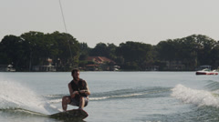USA, Florida, Orlando, Maitland Lake, Young man doing trick on wakeboard Stock Footage