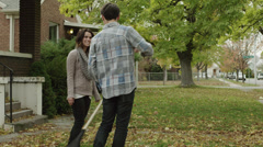 WS Young couple playing with leaves in front of house / Provo, Utah, USA Stock Footage