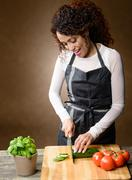happy woman cooking. healthy food - fresh cucumber - stock photo