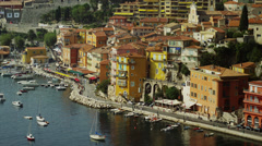 Wide shot of boats moored near buildings on waterfront / Villafranche, France Stock Footage