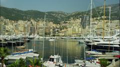 Wide shot of yachts moored in city harbor / Monte Carlo, Monaco Stock Footage