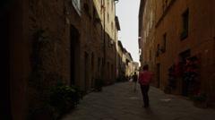 Medium shot of tourist taking photographs in Italian alley / Piensa, Tuscany, Stock Footage