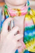 woman sprays perfume on silk scarf from atomizer - stock photo