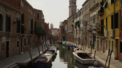 Medium shot of Venetian canal with moored boats / Venice, Italy Stock Footage