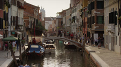 Medium shot of people crossing bridge on Venetian canal / Venice, Italy - stock footage