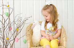 Young girl sit with white rabbit in wicker chair next to tree with toys. Studio. Stock Photos