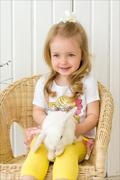 Young girl sit with white bunny rabbit on her lap in wicker chair. Studio. Stock Photos