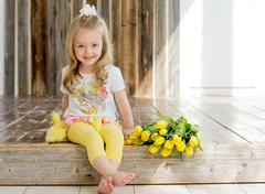 Girl sit on a wooden platform with yellow ducklings and tulips. Stock Photos