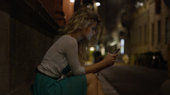 Close up of woman text messaging on cell phone at night / Milan, Italy Stock Footage