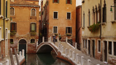Medium shot of people walking across Venetian bridge / Venice, Italy - stock footage