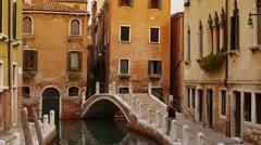 Medium shot of Venetian canal, buildings and bridge / Venice, Italy Stock Footage