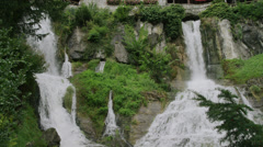 Slow motion/medium shot of waterfall and buildings on cliffs / St. Beatus Caves, Stock Footage
