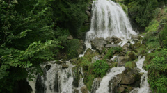 Slow motion/medium shot of waterfall and cliff / St. Beatus Caves, Switzerland Stock Footage