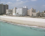 Stock Video Footage of MIAMI BEACH - 1980s: aerial boulevard, apartment buildings, beach
