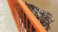 Trash, plastic and scrap of wood collect on pillar of bridge in the flood river. Stock Footage