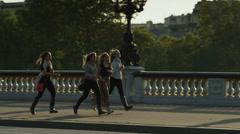 Tracking shot of tourists running on Paris bridge / Paris, France Stock Footage