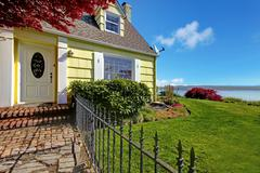 Yellow small classic home with water view and fence. Stock Photos