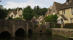 Slow motion/medium shot of people walking in town / Castle Combe, England, Stock Footage