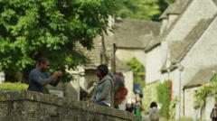 Medium shot of couple taking photographs on bridge in town / Castle Combe, Stock Footage