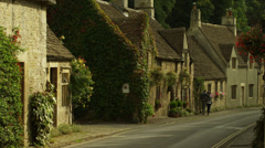 Medium shot of couple walking on sidewalk in town / Castle Combe, England, Stock Footage