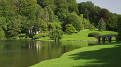Wide shot of green fields and bridge over tranquil lake / Stourhead, England, Stock Footage