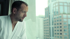 Young sad, pensive man by the window looking at cityscape HD Stock Footage