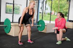 Crossfit woman lifts weights with personal trainer - stock photo