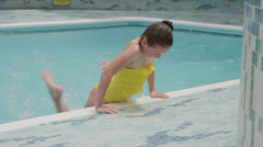 Panning shot of girl jumping into swimming pool / , Mexico, Stock Footage