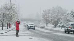 Snow falling on woman crossing busy urban street / Orem, Utah, United States, Stock Footage
