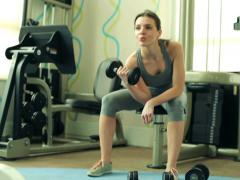 Young fit woman exercising with dumbbel in the gym NTSC Stock Footage